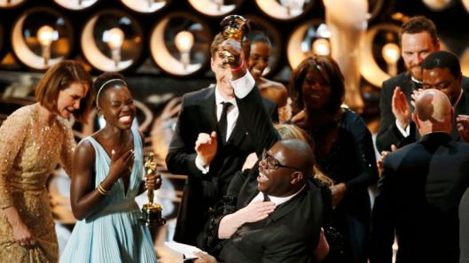 Director and producer McQueen celebrates after accepting the Oscar for best picture with Nyong'o at the 86th Academy Awards in Hollywood